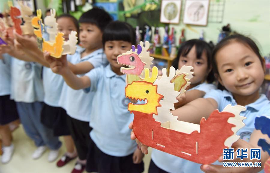6月14日,合肥市经开区中环城幼儿园的小朋友们展示自己制作的微型彩绘龙舟。