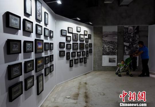 图为重庆老照片吸引市民驻足。 周毅 摄