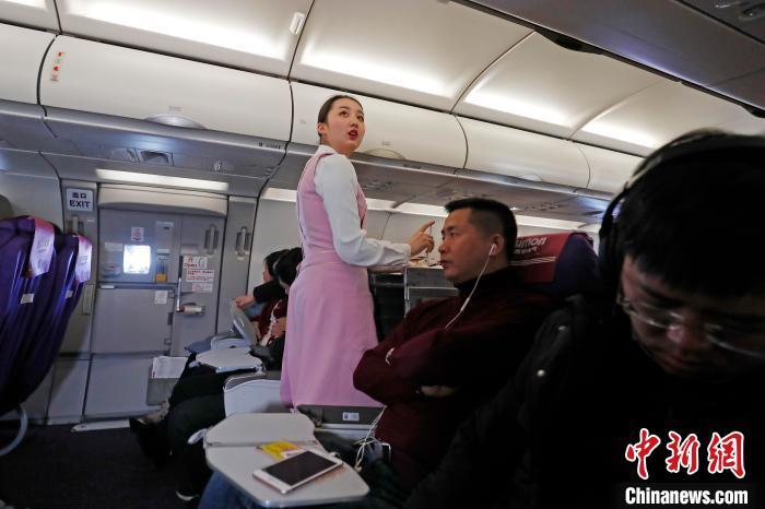 王姝樱在客舱里记下还在熟睡的旅客,以便旅客醒来第一时间为其服务。 殷立勤 摄